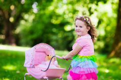 Little girl pushing a toy stroller wth doll Royalty Free Stock Photo