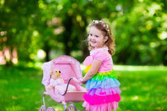 Little girl pushing a toy stroller wth doll Stock Photography