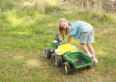 Little girl pushing a tractor Stock Photo