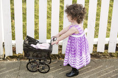 Little girl pushing a vintage stroller Royalty Free Stock Image