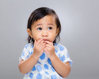 Little girl put finger into mouth Stock Images
