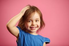 Little girl put her hand to head, smiles, has an expressive look, remembered something or came up with an idea. Portrait of smart child on pink isolated Stock Photography