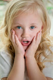 The little girl put her hands to her cheeks in surprise. Stock Photos