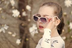 Little girl put sunglasses in spring summer nature.  royalty free stock image