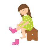Little girl puts on boots Royalty Free Stock Photography