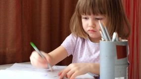 Little girl puts colored pencils in jar stock video footage
