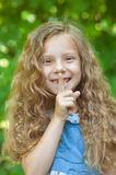 Little girl puts finger to lips Stock Image