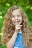 Little girl puts finger to lips Stock Image