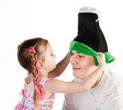 Little girl puts on the funny cap to her father isolated Royalty Free Stock Images
