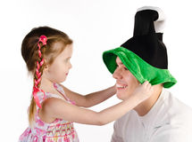 Little girl puts on the funny cap to her father isolated Stock Photo