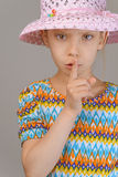 Little girl puts index finger to lips Stock Photo