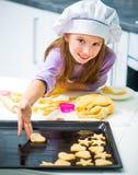 Little Girl Puts On Baking Cookies Stock Photography
