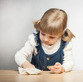 Little girl puts things in order with duster Stock Photos