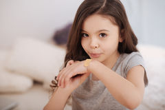 Little girl putting adhesive bandage on her injury at home Stock Photo