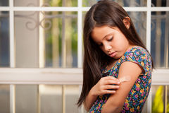 Little girl putting a band-aid on. Cute little acting all sad and girl putting a band-aid on her arm Stock Photo