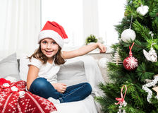 Little girl putting christmass tree ornaments royalty free stock images