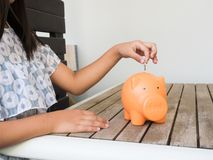 Little girl putting coin into piggy bank for saving with pile of royalty free stock photography