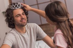 Dad and daughter. Little girl is putting a crown on her handsome dad who is smiling while they are playing together at home royalty free stock photography