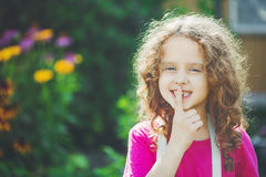 Little girl putting finger up to lips and ask silence. Toning ph Royalty Free Stock Photo