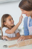 Little girl putting flour on the nose of her mother Royalty Free Stock Photography
