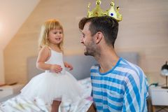 Little girl putting golden crown on dad`s head royalty free stock photo