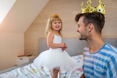 Little girl putting golden crown on dad`s head royalty free stock images