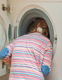 Little girl putting head into washing machine. Royalty Free Stock Photography