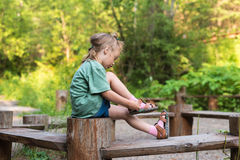 Little girl putting her sandal on. She is sitting on a wooden round bench in a summer forest Stock Images