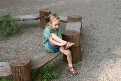 Little girl putting her sandal on. She is sitting on a wooden round bench in a summer forest Stock Photo