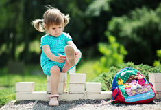 Little girl putting on her sandals Stock Images