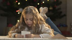 Little girl putting letter to Santa into envelope, faith in Christmas miracle. Stock footage stock video footage