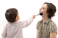 Little girl putting on the makeup to her mother isolated Royalty Free Stock Image