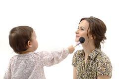 Little girl putting on the makeup to her mother isolated Stock Photography