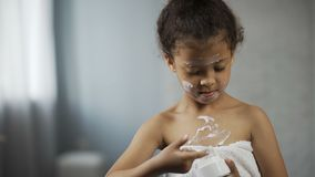 Little girl putting moisture cream on body and face, copying mother behaviour stock footage