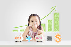 Little girl putting money on a piggy bank with a new year 2015. Saving concept from 2014 until 2015 drawing Stock Image