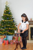 Little girl putting out cookies milk for santa. With christmas tree and fireplace in background Royalty Free Stock Photos