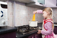 Little Girl Putting Pasta In The Pot Stock Image