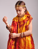Little girl putting on traditional Indian clothing and jeweleries Stock Image