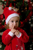 Little girl putting wishes under Christmas tree Royalty Free Stock Image