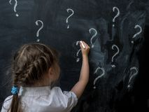 Little girl with question marks on blackboard. Concept for confusion, brainstorming and choice. Stock Photo