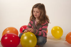 Little girl quietly tying balloon Stock Image