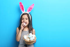 Little girl with rabbit ears. Beautiful little girl with rabbit ears and easter eggs on blue background Royalty Free Stock Images