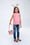 Little girl with rabbit ears holding basket of eggs Royalty Free Stock Photo