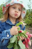 Little girl with radishes stock photography