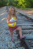 Little Girl On Railroad Track. This little girl enjoys looking for treasure along the railroad track that runs behind her MiMi`s house. She enjoys listening for Royalty Free Stock Photography