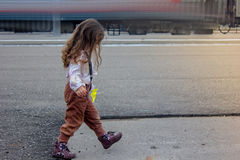 Little girl on railway station with the blured train on background. Stock Photo