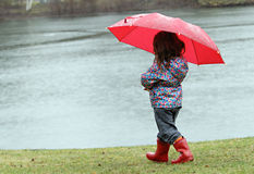 Little girl in the rain. With red boots and umbrella walking toward a pond Royalty Free Stock Image