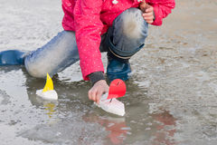 Little girl in rain boots playing with ships in the spring water puddle Stock Photos