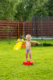Little girl in the rain in a red basin on grass Royalty Free Stock Image
