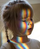 Little girl with rainbow . Little girl with rainbow light on his face Royalty Free Stock Images